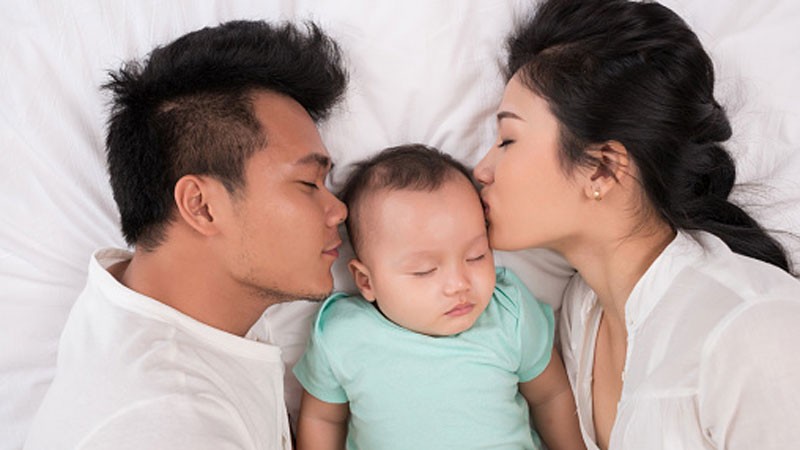 A baby with its eyes closed lying in a bed being kissed by its parents who are lying on both sides.